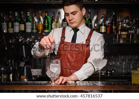Bartender cooling cocktail glass with ice #457816537