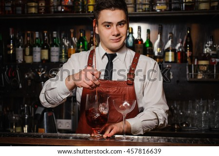 Bartender is stirring cocktails on the bar counter #457816639