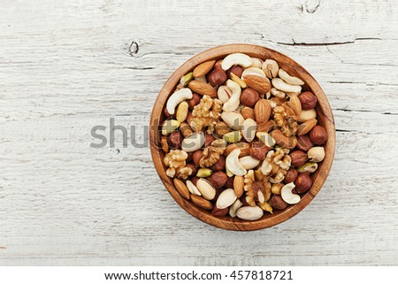 Wooden bowl with mixed nuts on white table from above. Healthy food and snack. Walnut, pistachios, almonds, hazelnuts and cashews. Royalty-Free Stock Photo #457818721