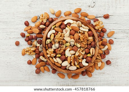 Wooden bowl with mixed nuts on white table top view. Healthy food and snack. Walnut, pistachios, almonds, hazelnuts and cashews. Royalty-Free Stock Photo #457818766