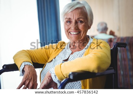 Smiling senior woman on a wheelchair looking at camera #457836142