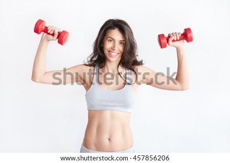 Smiling athletic woman pumping up muscles with red dumbbells isolated on white background. Strong fit brunette female fitness trainer #457856206