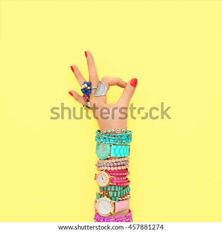Fashion. Trendy wrist watches, jewelry, female hand, OK gesture, accessories set. Minimal design. Stylish summer fashionable woman. Creative art shopping concept on yellow, summertime Royalty-Free Stock Photo #457881274