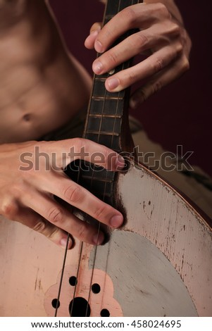 Man's hands with folk musical instrument domra #458024695