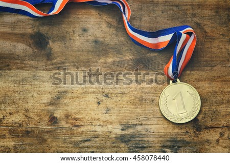 top view image of medal gold over wooden textured table #458078440