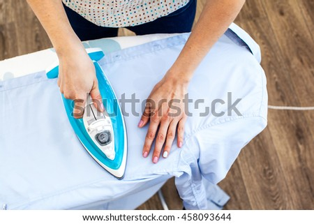 Closeup of woman ironing clothes on ironing board #458093644