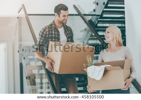 Moving to a new home. Happy young couple holding cardboard boxes while going down the stairs #458105500