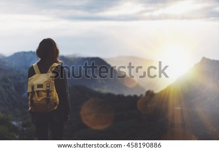 Hipster young girl with backpack enjoying sunset on peak of foggy mountain. Tourist traveler on background view mockup. Hiker looking sunlight in trip in Spain country, mock up text. Picos de Europa Royalty-Free Stock Photo #458190886