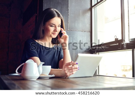 Young girl with cute smile talking on mobile phone while sitting alone near big window in coffee shop during free time and working on tablet computer.Happy female having rest in cafe.Lifestyle #458216620