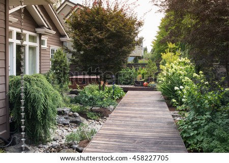 A long, narrow wooden deck in the backyard of a contemporary home. #458227705