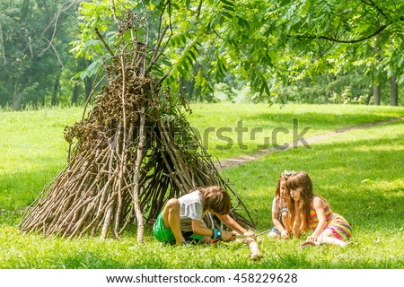 outdoor portrait of three happy kids - boy and girls - playing next to wooden stick hut house, looking like indian tepee, on natural background #458229628