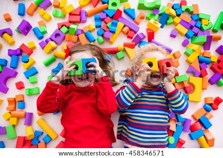 Happy preschool age children play with colorful plastic toy blocks. Creative kindergarten kids build a block tower. Educational toys for toddler or baby. Top view from above. #458346571