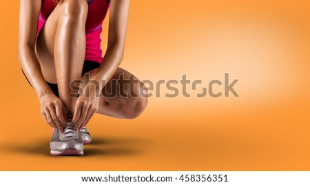 Running shoes - woman tying shoe laces. Closeup of female sport fitness runner getting ready for jogging #458356351