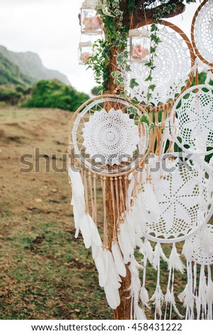 Tree decorated with dreamcatchers and glass jars filled with roses #458431222