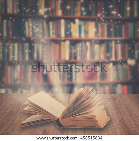 Open book on wooden book shelf with magic light, retro toned #458515834