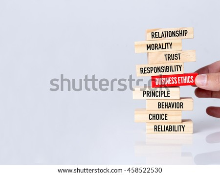 Businessman Building BUSINESS ETHICS Concept with Wooden Blocks #458522530