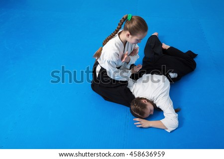 Two girls in black hakama practice Aikido Royalty-Free Stock Photo #458636959
