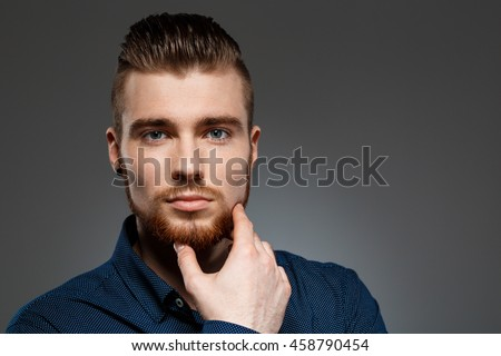 Young successful businessman posing over dark background. Copy space. #458790454