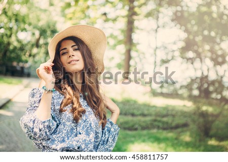 Elegant female with a hat on her head in park. Young woman with long hair,  smiling and posing. #458811757