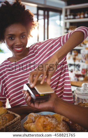 Smiling woman paying bill through smartphone using nfc technology in cafe #458821765