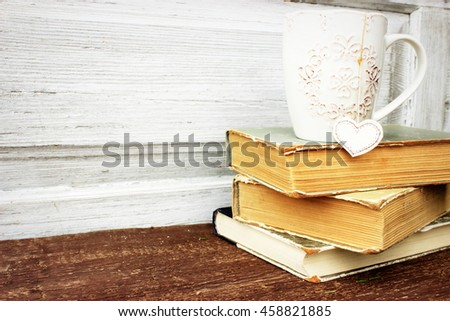 Romantic composition with stack of vintage books with very old paper and covers and cup of hot tasty tea in ceramic cup with label in heart shape on wooden background. Copy space