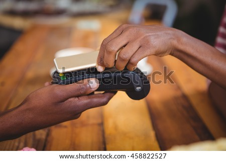 Woman paying bill through smartphone using nfc technology in cafe #458822527