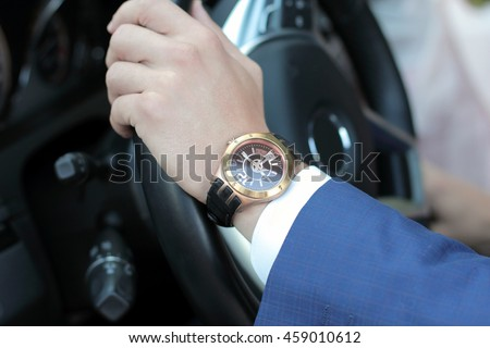Businessman driving his car, hand on the steering wheel. Hand with golden watch. Business concept. Royalty-Free Stock Photo #459010612
