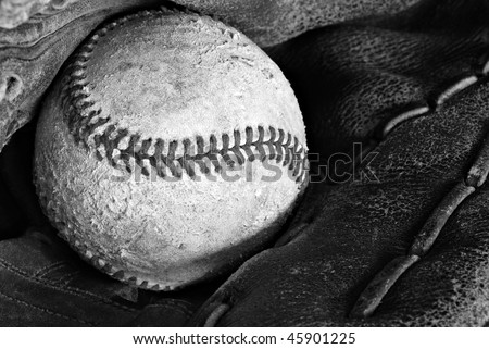 Black and white image of old weathered baseball in vintage glove.   Macro with shallow dof.  Focus on stitching.