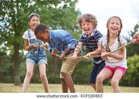 Children playing tug of war at the park Royalty-Free Stock Photo #459100483