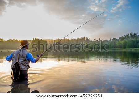 Young man flyfishing at sunrise Royalty-Free Stock Photo #459296251