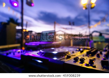 Blurred picture of professional sound system equipment for party outdoor at sunset - Defocused image - Concept of nightlife with music and entertainment on the beach - Original color lights