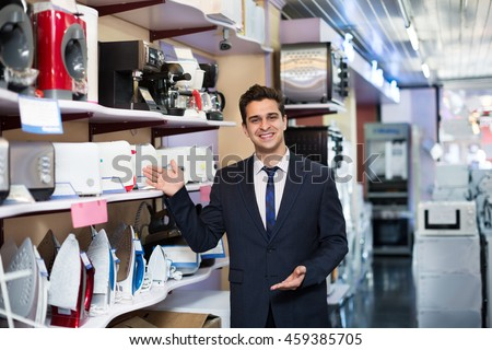 Successful male seller at a household appliances section of a supermarket  #459385705