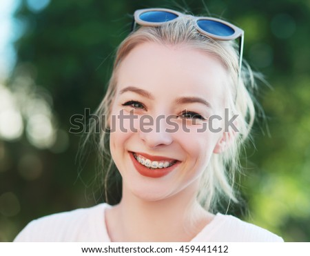 beautiful blond teen girl with braces on her teeth smiling #459441412