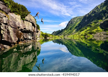Young couple jump together into lake in mountains with beautiful blue water and reflexion.  Royalty-Free Stock Photo #459494017
