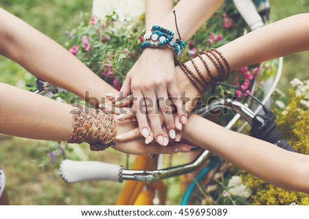 United hands of young females. Stylish hands of girlfriends in boho hippie bracelets near bicycle handlebar, top view. Togetherness and support, youth fashion and active lesiure. Women friendship Royalty-Free Stock Photo #459695089