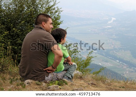 Father and son sitting on the hill watching the view #459713476