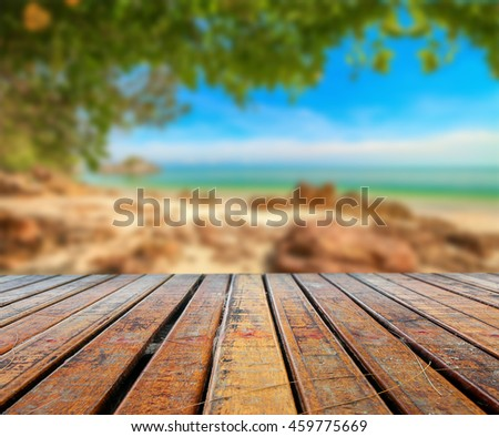 blurred beautiful beach with wooden plank under for put your products