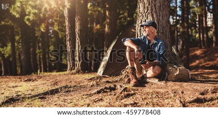 Portrait of senior man sitting by a tree with a tent in background. Mature man sitting at a campsite. #459778408