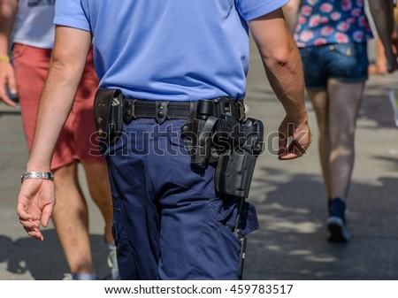 German police officer is walking in a main street of berlin and observing people. Close up picture from his gun and safety equipment.