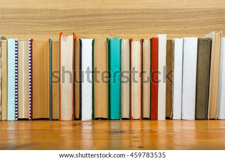 Composition with vintage old hardback books, diary, fanned pages on wooden deck table and beige background. Books stacking. Back to school. Copy Space. Education background. #459783535