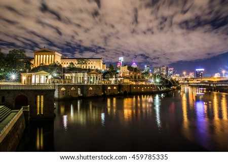 A nighttime view of the Philadelphia Museum of Art, with the city skyline behind it.