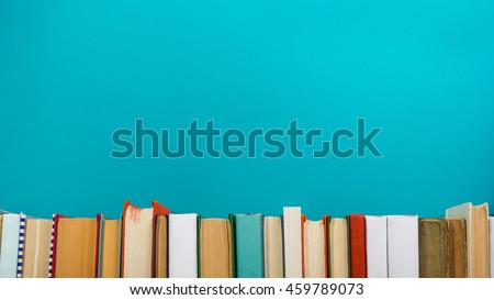 Simple composition of hardback books, raw of books on wooden deck table and blue background. Books stacking with no labels, blank spine Back to school Copy Space Education background Office supplies  #459789073