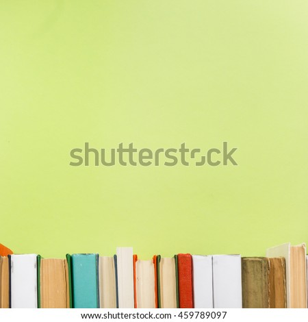 Simple composition of hardback books, raw of books on wooden deck table and green background. Books stacking with no labels, blank spine Back to school Copy Space Education background Office supplies  #459789097
