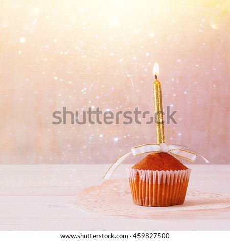 Birthday concept with cupcake and candle on wooden table. Glitter overlay