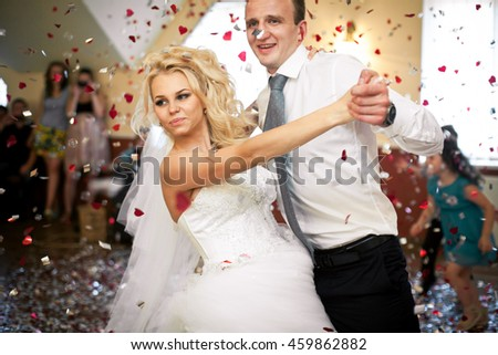 Groom bends gorgeous bride over dancing in the shower of confetti #459862882