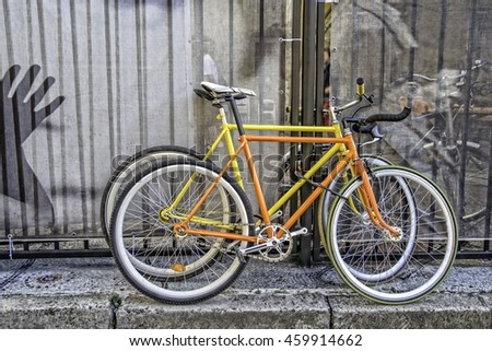 Bicycles with fixed gear . Two orange and yellow fixed gear bikes (fixy) locked on the pavement
