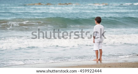 Pensive little boy standing on the beach, meditation, Spain #459922444