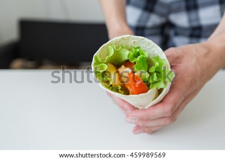 man cooking fast food rolls.  chicken nuggets, lettuce, tomato, cheese, Mexican tortillas #459989569