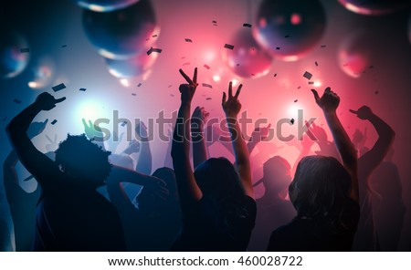 Young happy people are dancing in club. Nightlife and disco concept. Royalty-Free Stock Photo #460028722