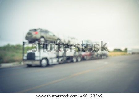 Blurred image big car carrier truck of new cars for batch delivery to dealership. Full load transport truck of new vehicles on country road. Automotive industry abstract background.Vintage filter look #460123369